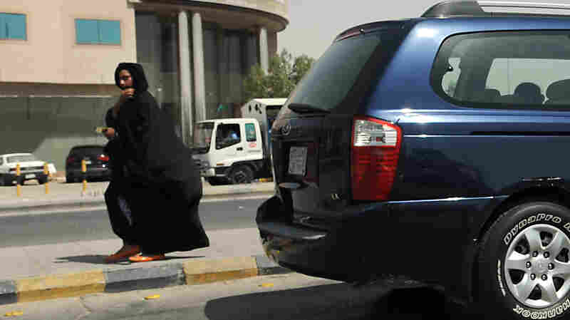 A Saudi woman walks past vehicles stopping at a traffic light in Riyadh, where there is a government ban on women driving.