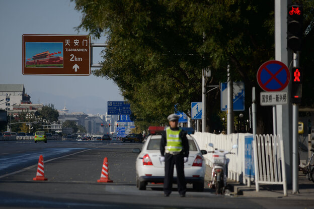 A police officer stands on an  avenue outside Tiananmen Square in Beijing, on Tuesday.