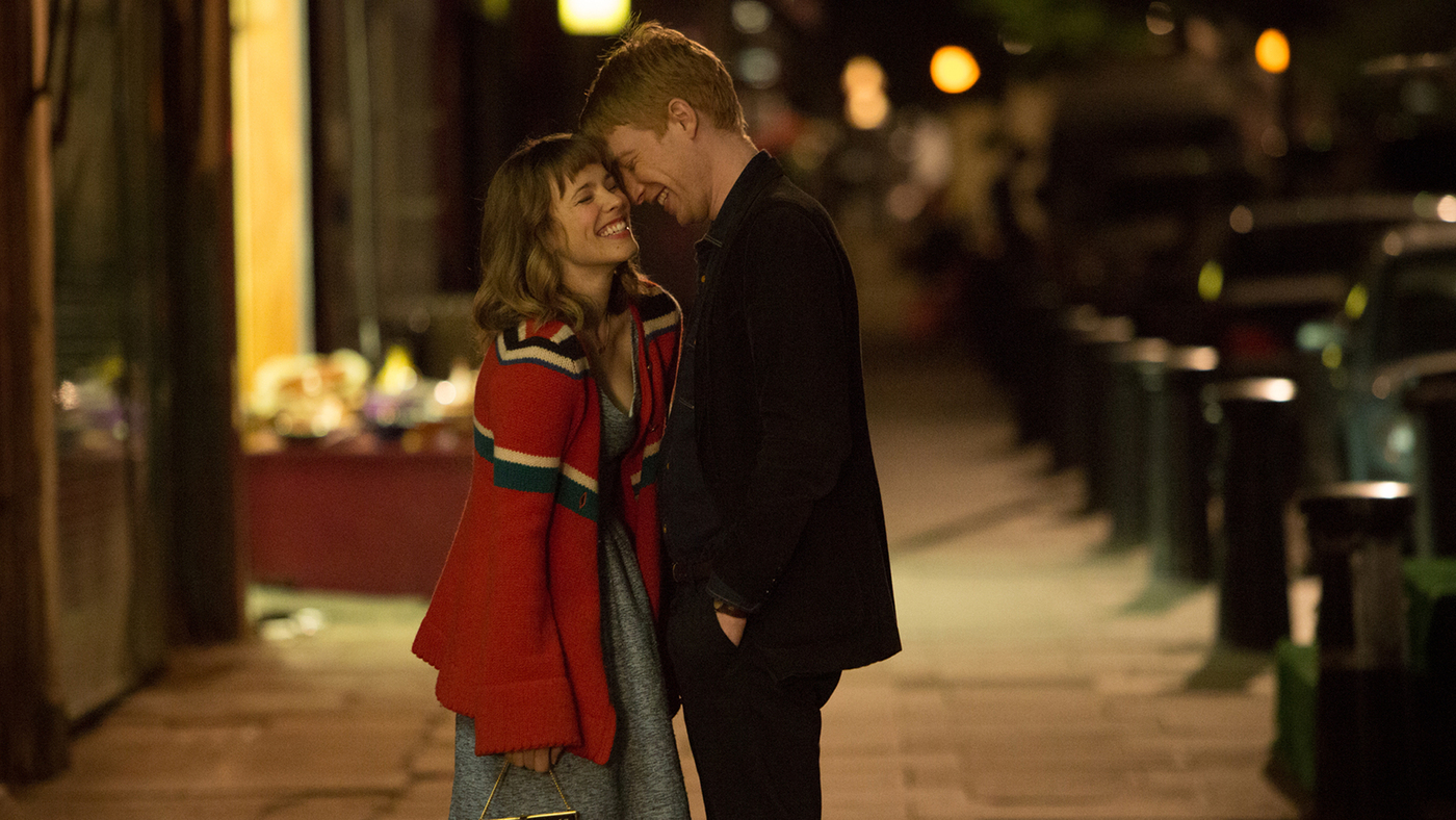 Rachel McAdams and Domhnall Gleeson in About Time (2013). Tim and Mary stand together on the street after a night out, softly lit by store fronts and street lamps. They lean into each other, laughing together.