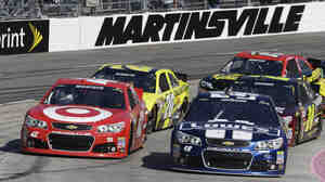 Sprint Cup Series driver Jimmie Johnson (48) and Juan Pablo Montoya (42) drive through turn four on a restart during the NASCAR Sprint Cup auto race at Martinsville Speedway in Martinsville, Va.