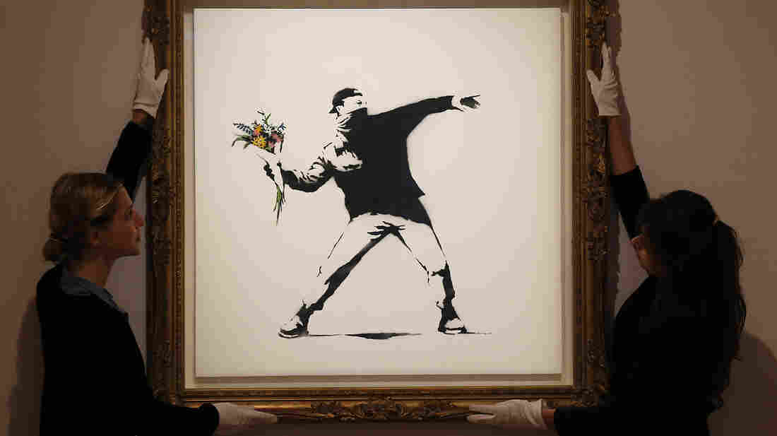 """A limited edition of Banksy's """"Love Is in the Air"""" sold for $249,000 at Bonhams auction house in London this summer. The artist offeed a version of the work for $60 on the sidewalk in New York Saturday."""