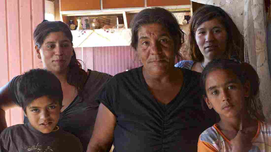 "Maria Souta (center), a Roma grandmother in her 50s, lives in a shack in the Roma camp near Corinth, Greece. She supports her family by picking aluminum cans out of the trash. ""I really want my children to get an education and get out of here,"" she says."