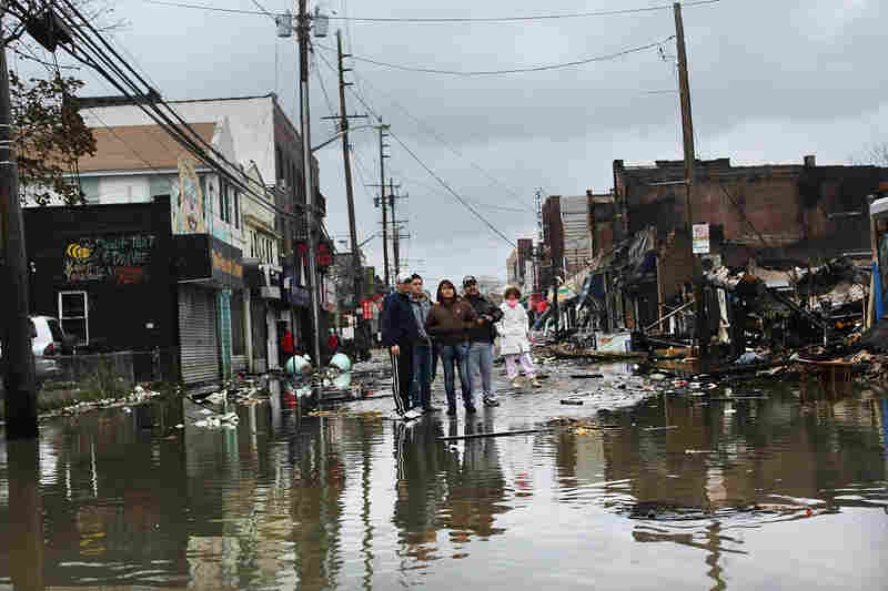Neighbors in the Rockaway section of Queens, N.Y., survey homes and businesses destroyed by Superstorm Sandy on Oct. 30, 2012.