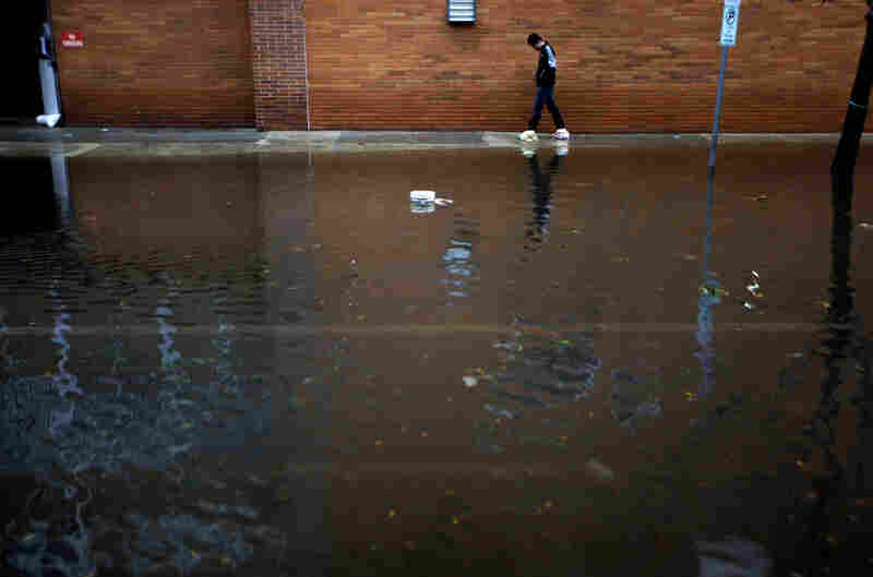 A resident traverses flooded streets as cleanup