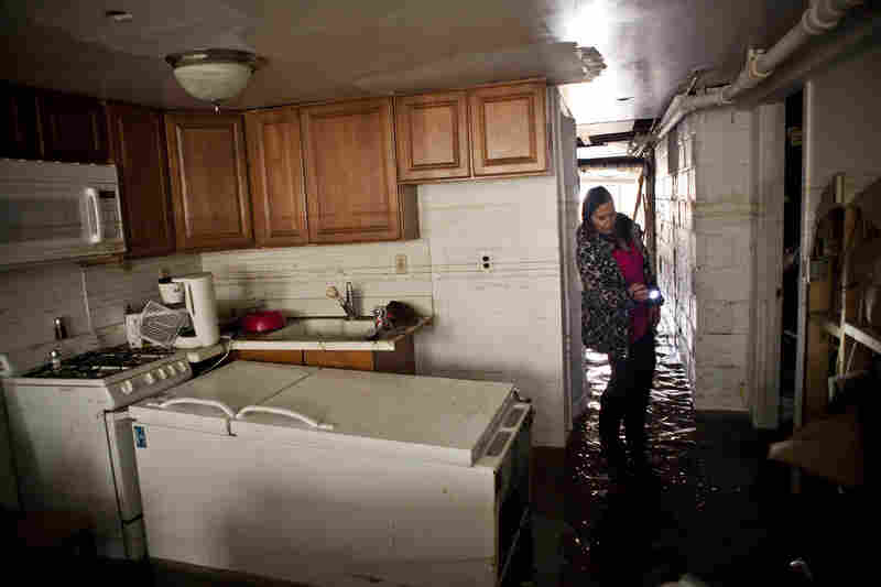 Jackie Hoey inspects the first floor of her Long Beach, N.Y., home, which experienced heavy flooding.