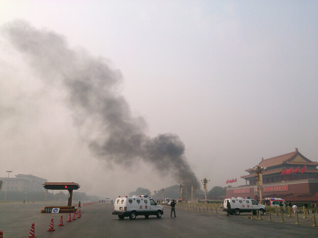 Police cars block off the roads leading into Tiananmen Square as smoke rises into the air after a vehicle crashed in front of Tiananmen Gate in Beijing on
