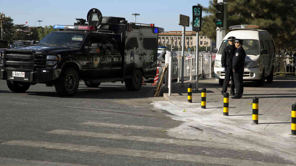 A vehicle from the Chinese police special tactical unit guards the sidewalk Tuesday where it is believed a car drove up before it plowed through a crowd and crashed and burned in Beijing's Tiananmen Square.