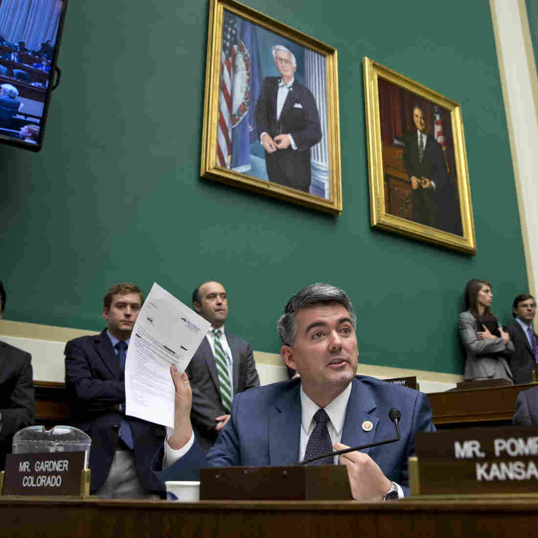 One person who got a letter canceling his health insurance was Rep. Cory Gardner, R-Colo. He holds up the letter during a congressional hearing Wednesday on insurance problems. He says his family chose to buy private insurance rather than use the congressional plan.