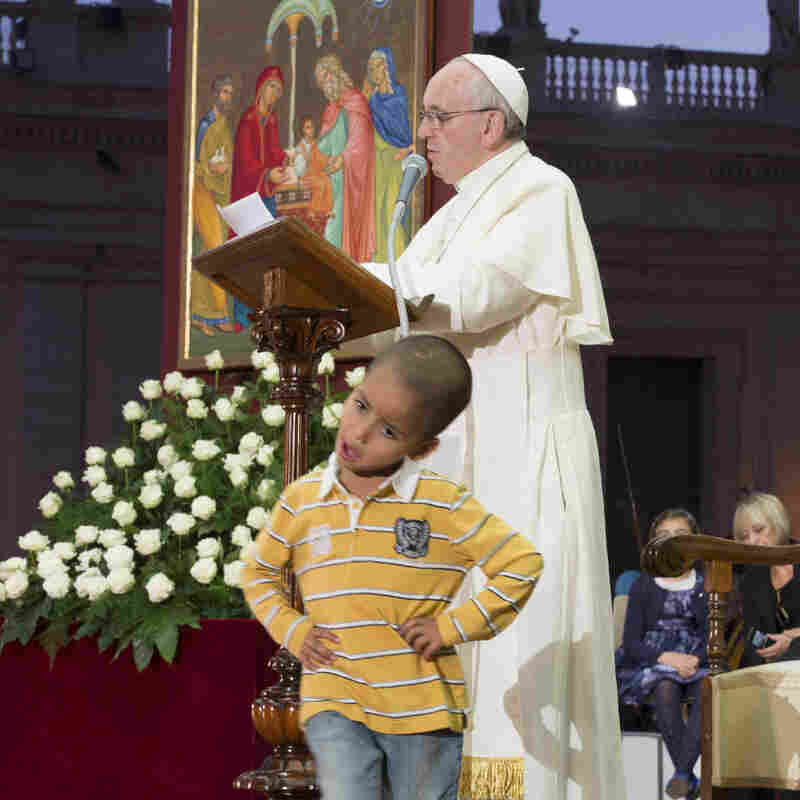 In this photo provided by the Vatican newspaper L'Osservatore Romano, Pope Francis reads his message as a young boy plays in front of him on the stage.