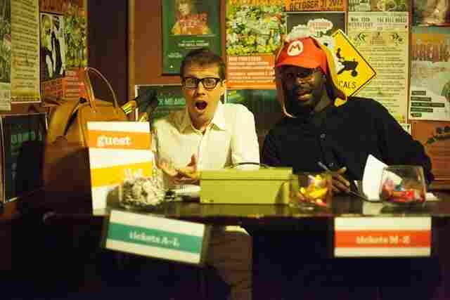 Producers Alvy (Josh Rogosin) and Tanooki Suit Mario (John Asante) from Annie Hall man the candy-clad ticket table at Ask Me Another's home venue, The Bell House.