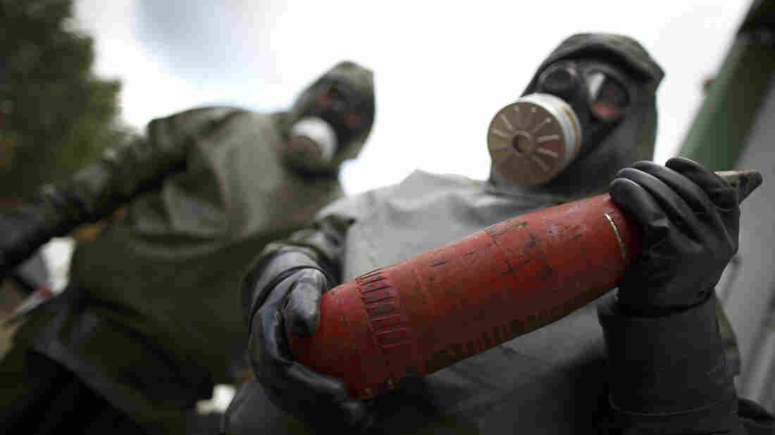 Workers in protective suits hold dummy munition during a demonstration at a chemical weapons disposal facility in Muenster, Germany, on Wednesday.
