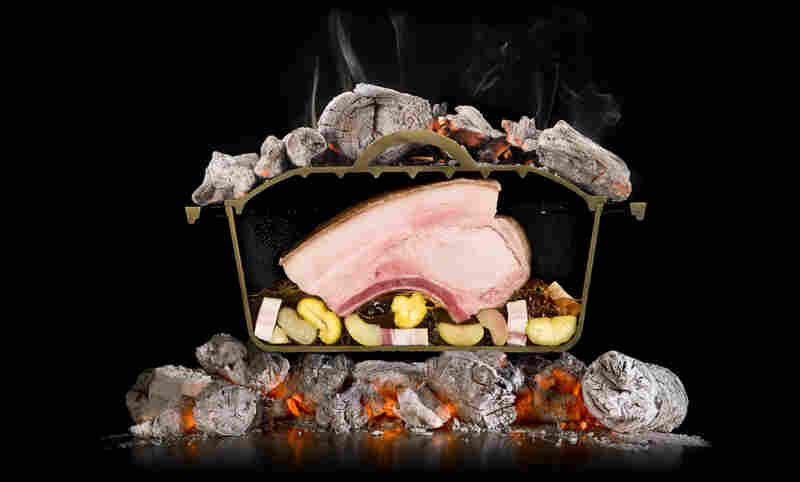 Photography or a food dramatization? An iron pot is sliced in half to show how a pork roast adsorbs heat when hot coals are placed above and below the meat.