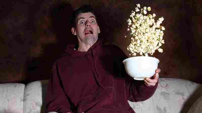 A man is so terrified by a movie he's watching that he throws all his popcorn in the air. (A waste of perfectly good popcorn.)