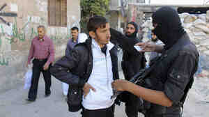 A Syrian fighter from the Islamist rebel group Jabhat al-Nusra inspects a resident's identification papers at a checkpoint in Aleppo on Oct. 26. Syria's Islamist fighters are generally better funded than their more moderate counterparts.