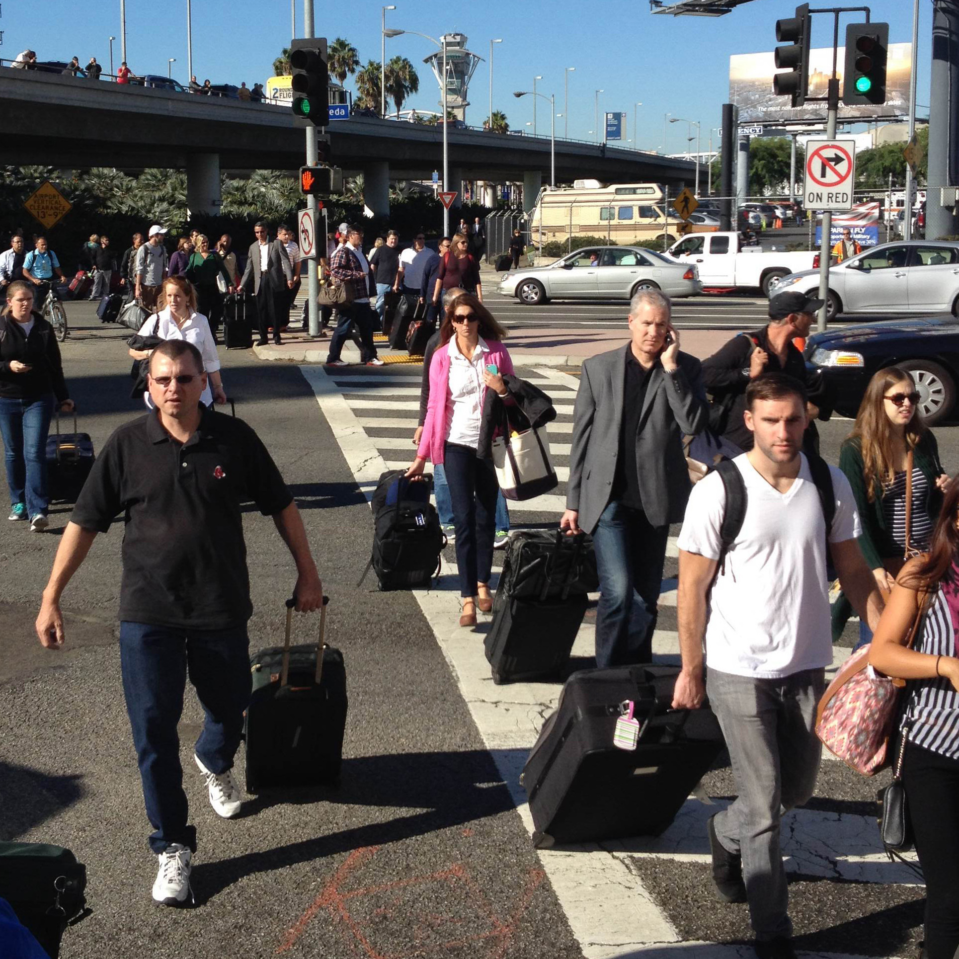 Travelers evacuate the area at Los Angeles International Airport after Friday's shooting incident.