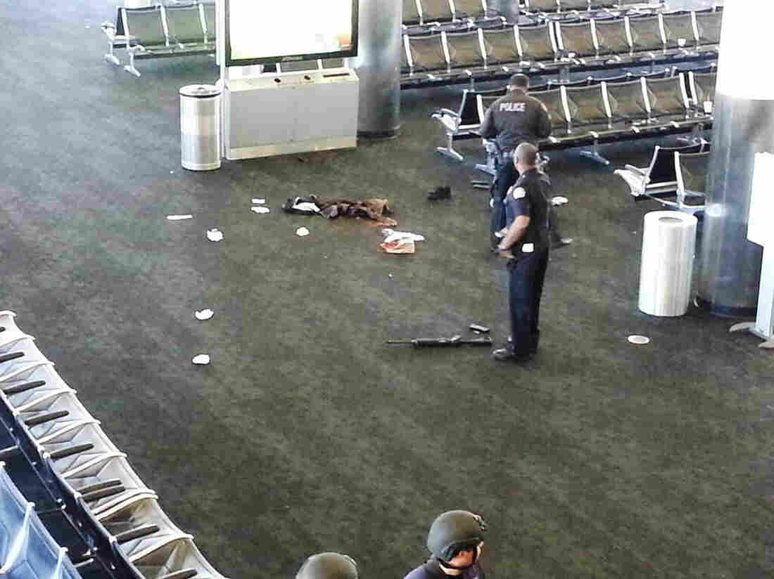 Police officers stand near an unidentified weapon in Terminal 3 of the Los Angeles International Airport on Friday. Officials said a gunman who opened fire in the terminal was wounded in a shooto