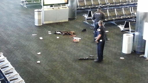 Police officers stand near an unidentified weapon in Terminal 3 of the Los Angeles International Airport on Friday. Officials said a gunman who opened fire in the terminal was wounded in a shootout with police and taken into custody. (AP)