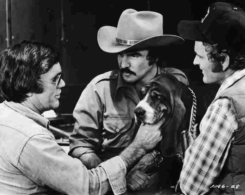 Director Hal Needham lines up a shot with actors Burt Reynolds, Jerry Reed and Happy the dog on the set of the 1977 movie Smokey and the Bandit.