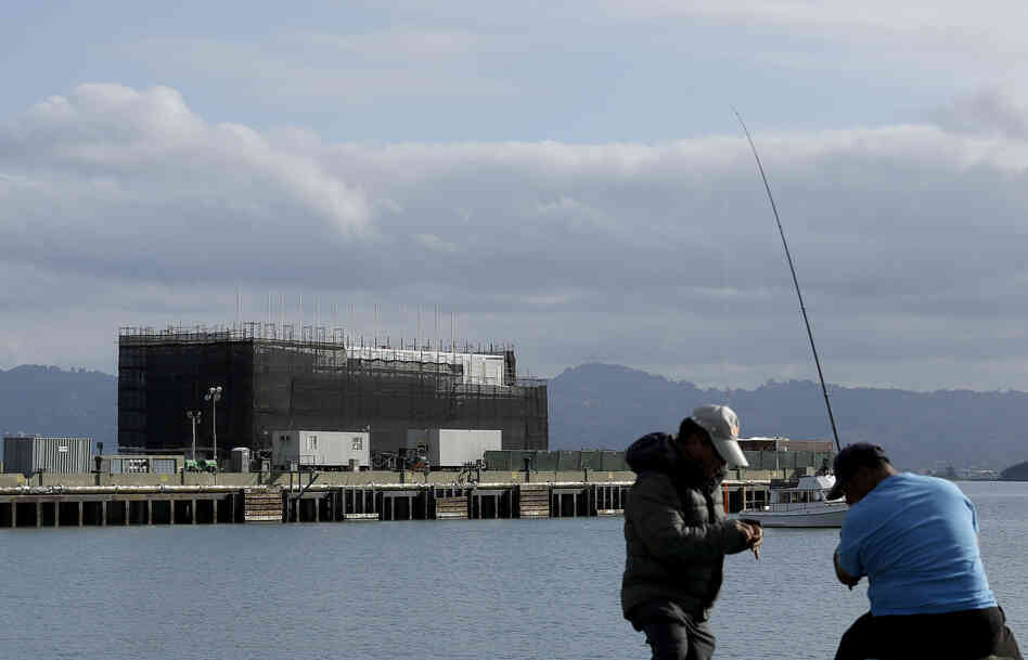 "Two men fish in the water in front of a barge on Treasure Island in San Francisco on Tuesday. An unnamed source tells CBS the barge carries a building ""constructed of interchangeable 40-foot shipping containers that can be assembled and"