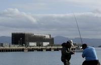 Two men fish in the water in front of a barge on Treasure Island in San Francisco on Tuesday. An unnamed source tells CBS the barge carries a building