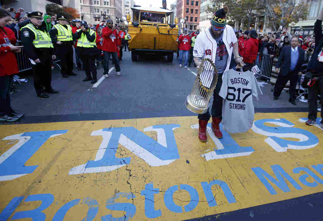 Boston Red Sox's Jonny Gomes places the championship trophy and a Red Sox baseball jersey at the Boston Marathon Finish Line during a pause in their World Series victory rolling rally in Boston on Saturday.