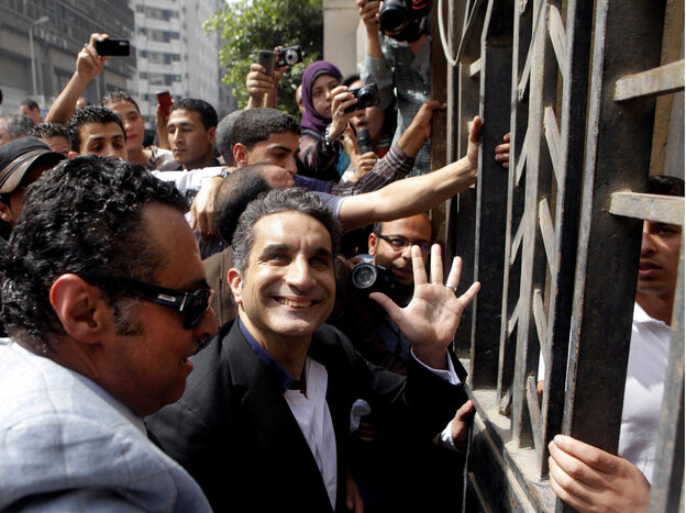 Television satirist Bassem Youssef waves to supporters as he enters Egypt's state prosecutors office in March of 2013.