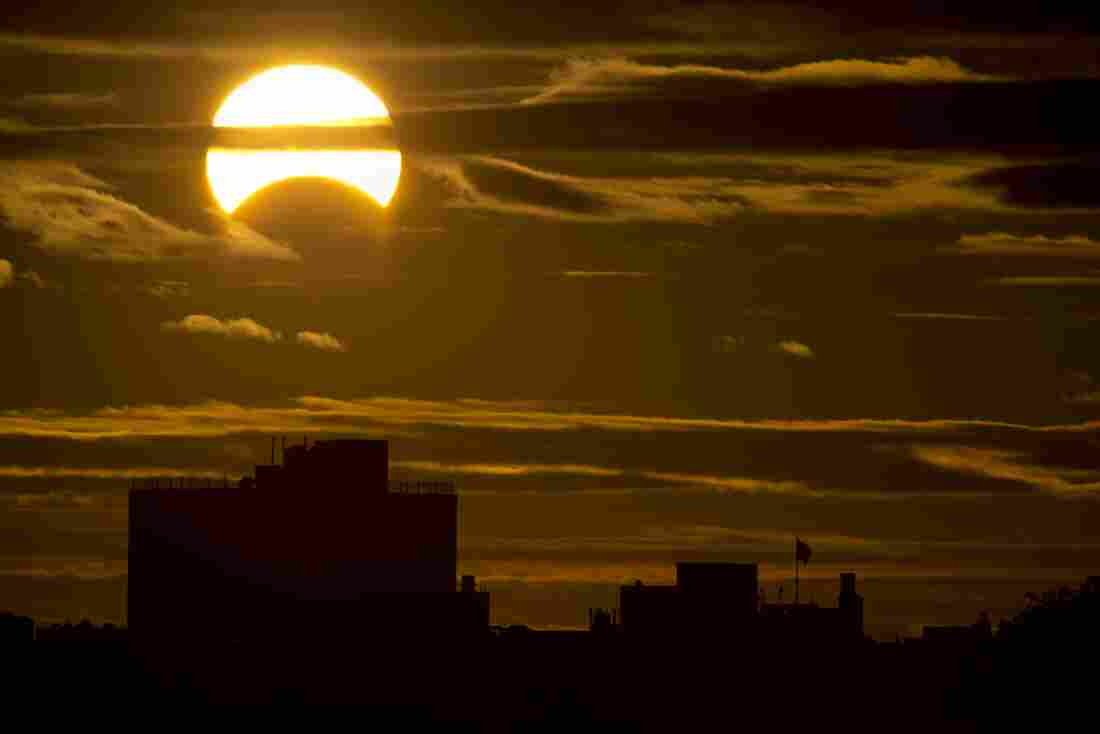 A partial Solar eclipse is seen just after sunrise over the Queens borough of New York across the East River on Sunday in New York.