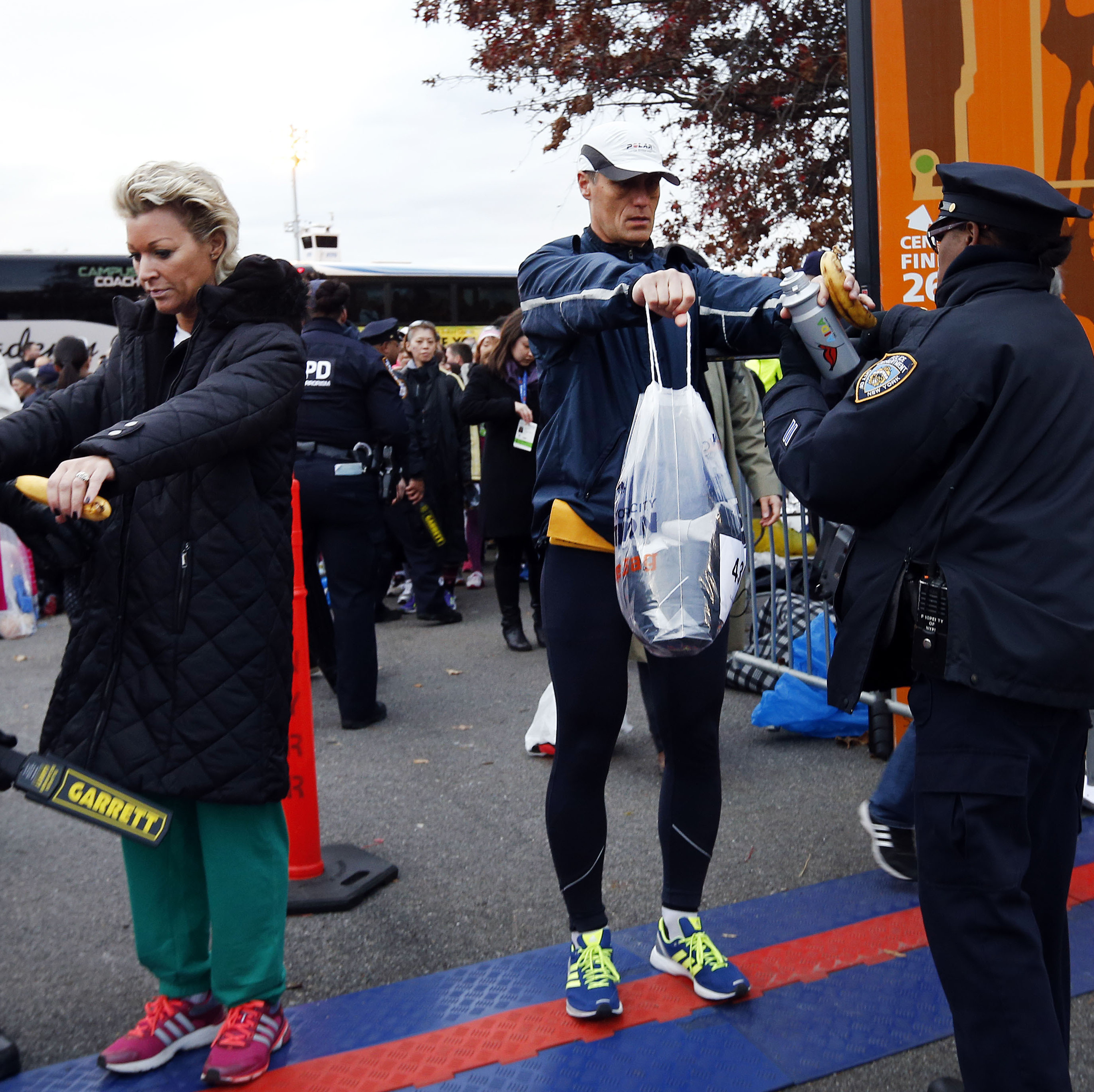 Runners are screened by police officers as they arrive for the New York City Marathon on Sunday.