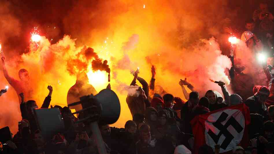 Spartak Moscow soccer fans burn flares and wave a flag with a swastika (lower right) during a game with Shinnik Yaroslavl in Yaroslavl, Russia, on Oct. 30. It's one of several recent violent or racist incidents at sporting events in a country that's hosting the 2014 Winter Olympics and the 2018 World Cup.