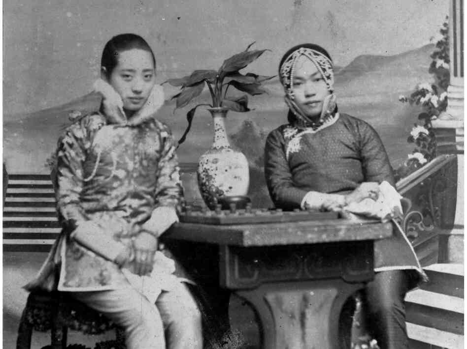 Amy Tan's grandmother (right) poses with a friend against a painted backdrop. Her outfit was an ensemble traditionally reserved for courtesans — although it could have been a costume borrowed for this portrait.