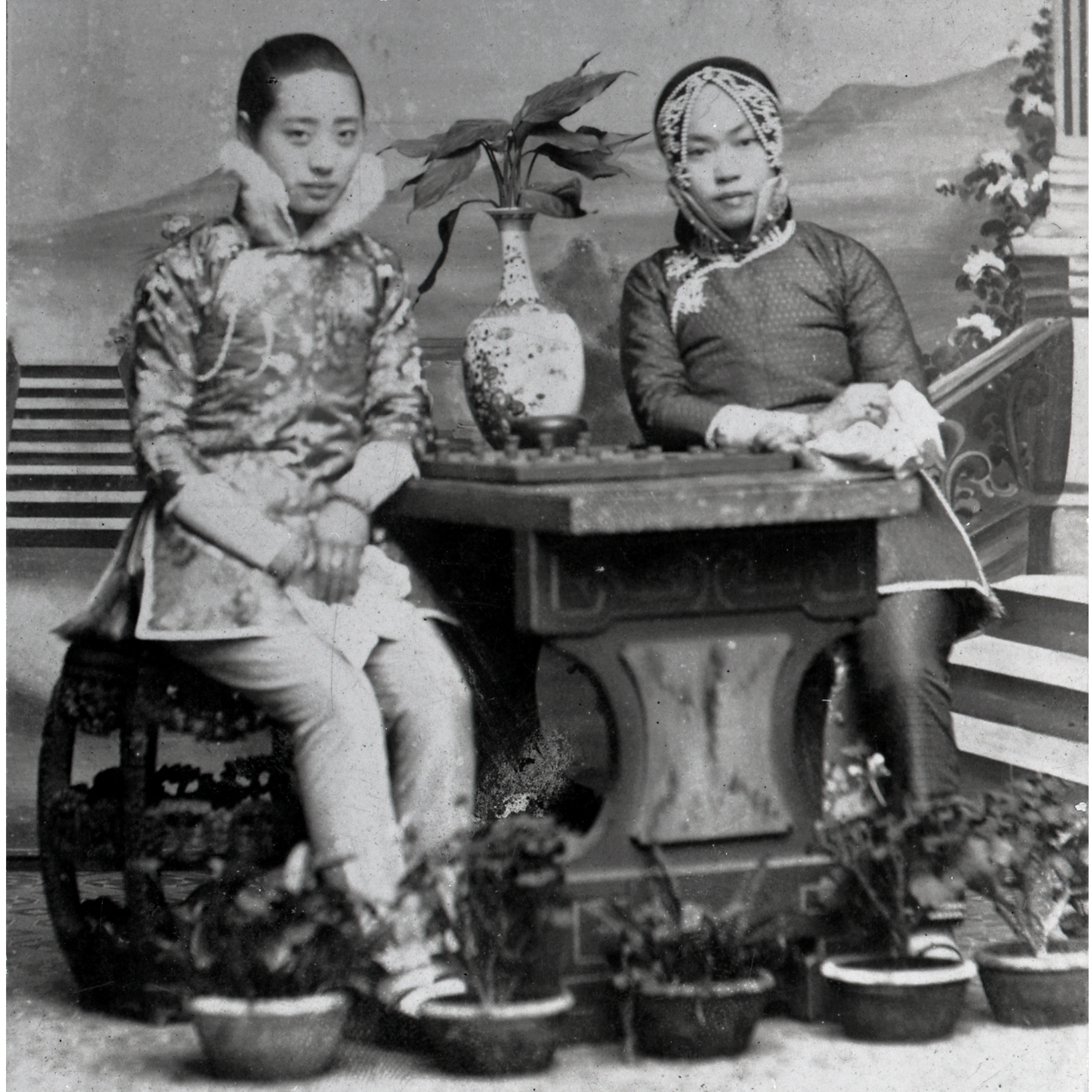 Amy Tan's grandmother (right) poses with a friend against a painted backdrop. Her outfit was an ensemble traditionally reserved for courtesans -- although it could have been a costume borrowed for this portrait.