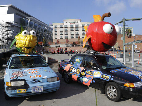 "Cindy Black, right, and Jill Hill park a car with a giant apple on top that promotes a ""yes"" vote on I-522 in Washington state — which would require genetically engineered foods to be labeled as such — on Oct. 17 in Tacoma, Wash."