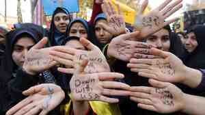 "Iranian girls show their hands, marked with the words ""Down with USA,"" at Monday's demonstration in Tehran."