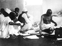Mohandas K. (Mahatma) Gandhi shown using a spinning wheel in 1933 shortly after his release from prison.