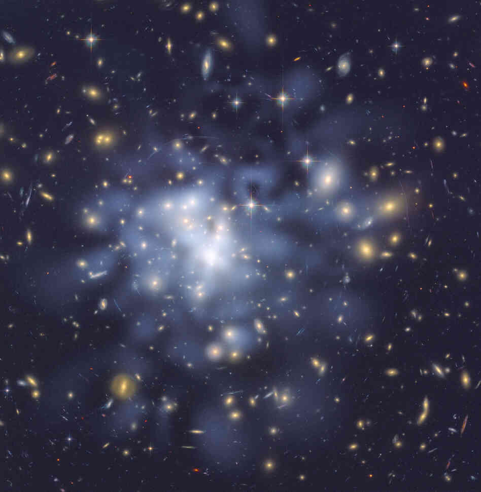 This Hubble image from 2002 shows dark matter in the galaxy cluster Abell 1689. The cluster, 2.2 billion lightyears from Earth, contains about 1,000 galaxies and trillions of stars. Hubble cannot see dark matter directly. Astronomers inferred its location by analyzing the effect of gravitational lensing. The densest concentration of dark matter (seen as a blue tint) is in the cluster's core.