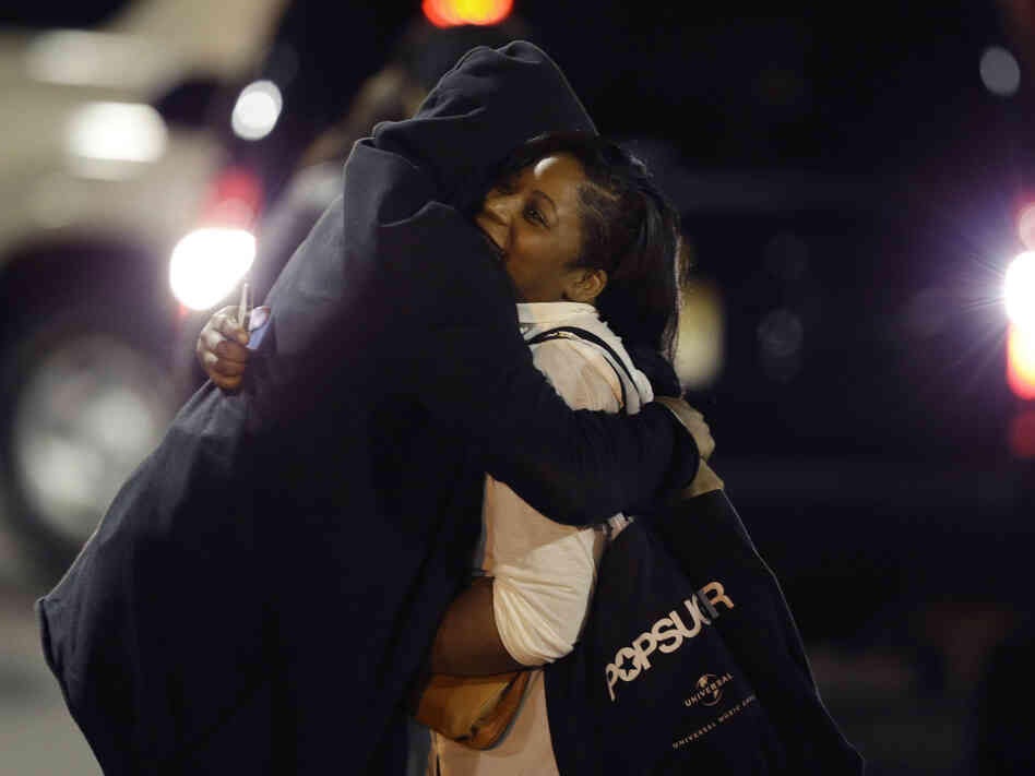 Two people hug early Tuesday after reaching safety outside the Garden State Plaza Mall in Paramus, N.J. A gunman fired several shots there Monday night, sending shoppers and employees scrambling. No one was hurt. Hours later, the suspected gunman's body was found. Police believe he shot himself.