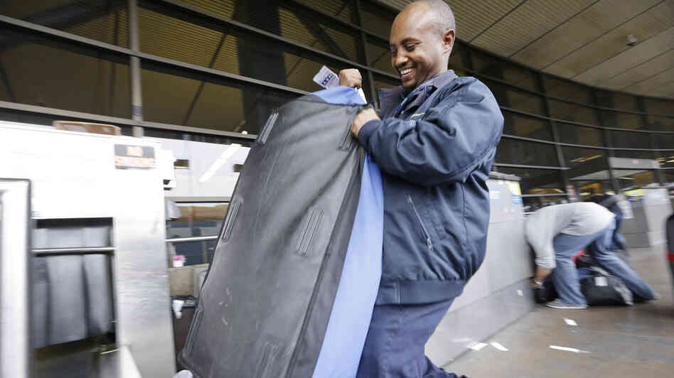Skycap Biniyam Yehuala hefts a traveler's bag at Seattle-Tacoma International Airport. On Tuesday, voters in SeaTac, Wash., approved a minimum wage of $15 an hour for roughly 6,300 low wage workers' whose jobs are at or near the airport.