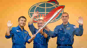 Flight Engineer Koichi Wakata of the Japan Aerospace Exploration Agency, left, Soyuz Commander Mikhail Tyurin of the Russian space agency Roscosmos, and Flight Engineer Rick Mastracchio of NASA, hold the Olympic torch that will be flown with them to the International Space Station, during a press conference on Wednesday.