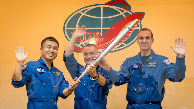 Flight Engineer Koichi Wakata of the Japan Aerospace Exploration Agency, left, Soyuz Commander Mikhail Tyurin of the Russian space agency Roscosmos, and Flight Engineer Rick Mastracchio of NASA, hold the Olympic torch that will be flown with them to the International Space Statio