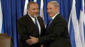 Israeli politician Avigdor Lieberman (left) shakes hands with Prime Minister Benjamin Netanyahu last year. Lieberman was acquitted of fraud charges on Wednesday and is expected to return to his old job as foreign minister.