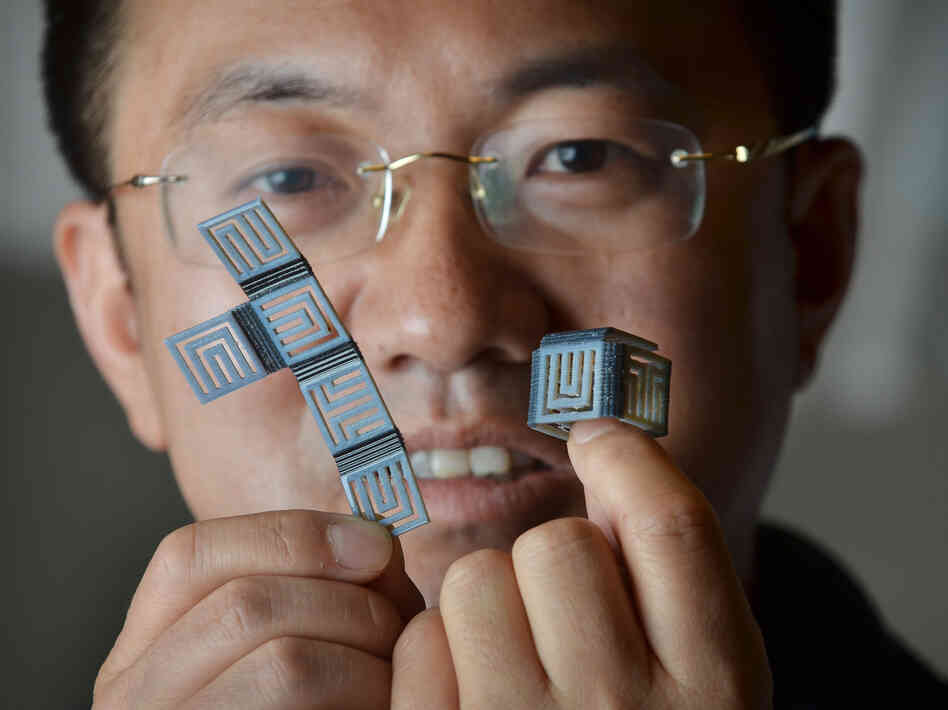 "H. Jerry Qi, associate professor of mechanical engineering at Colorado University, holds simple models printed using polymers that have ""shape memory."" The flat piece on the left can reshape itself into a box with the application of heat."