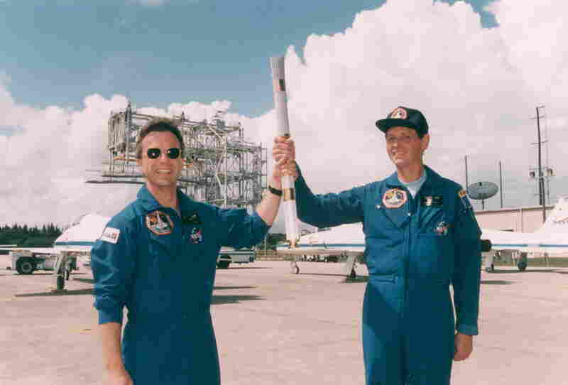 Payload specialists Robert Brenton Thirsk, left, and Jean-Jaques Favier hold the Olympic torch they brought to space aboard Space Shuttle Columbia in 1996.