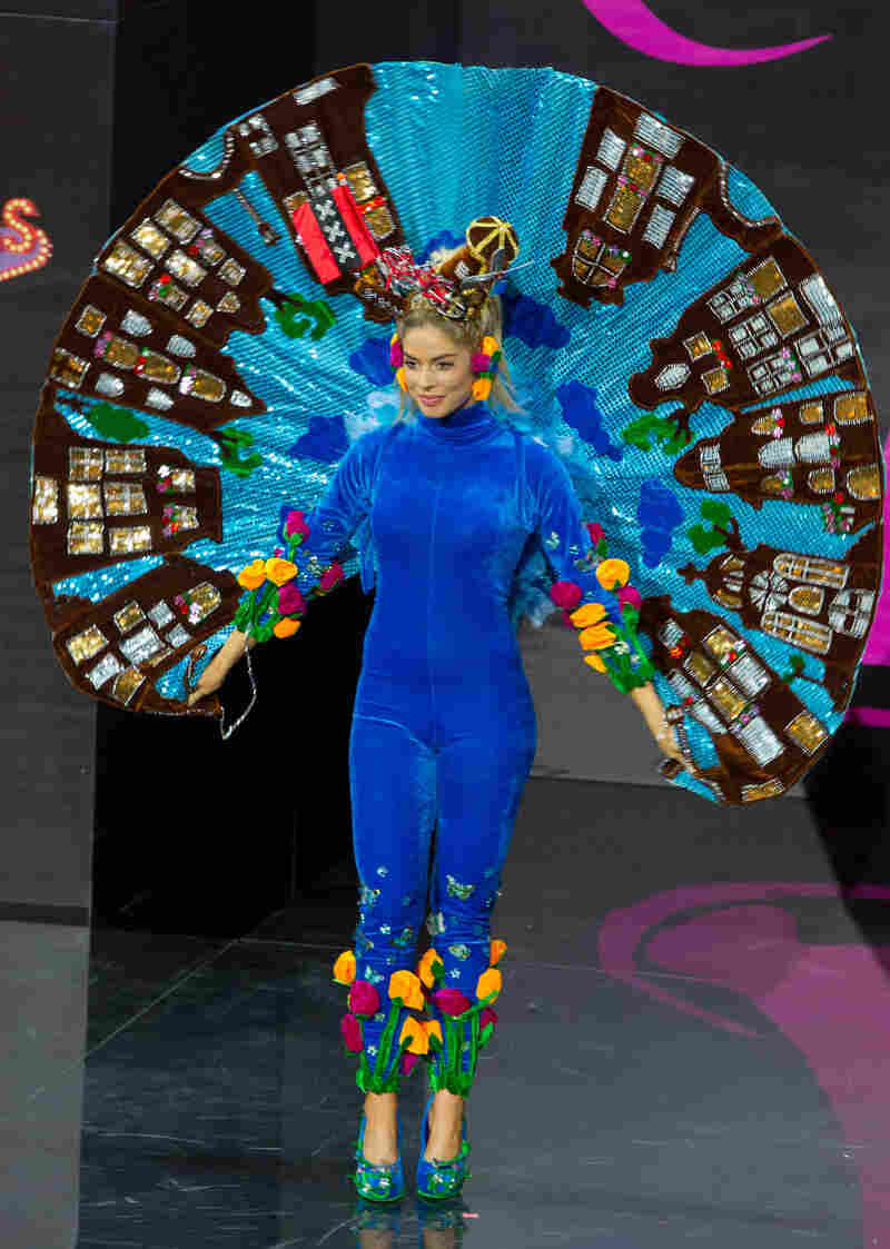 I just want you to pause and appreciate that she is wearing what appears to be a velvet jumpsuit with a standing Elvis cape made of buildings, a windmill and a bicycle on her head, and tulips on her pants. (Miss Netherlands: Stephanie Tency)