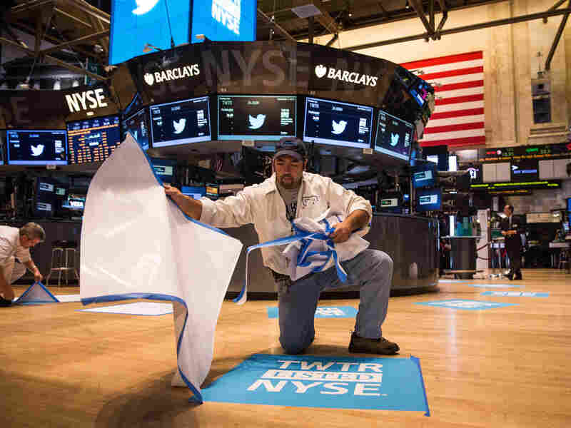 A worker unveils a floor mat bearing the logo of Twitter on the floor of the New York Stock Exchange.