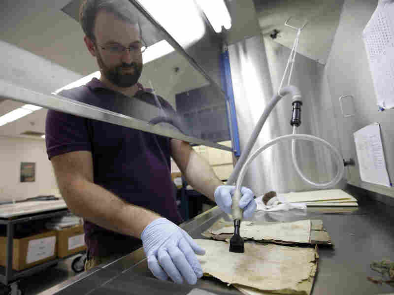 Patrick Brown, a conservation technician, works on Iraqi Jewish documents at the National Archives in College Park, Md., on  Sept. 30.