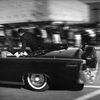 The limousine carrying President John F. Kennedy races toward the hospital after he was shot in Dallas on Nov. 22, 1963, with Secret Service agent Clint Hill riding on the back.