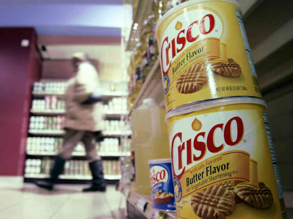 Crisco was the original product made with partially hydrogenated soybean oil, which contains trans fats. Today, Crisco has only small amounts of the fats.