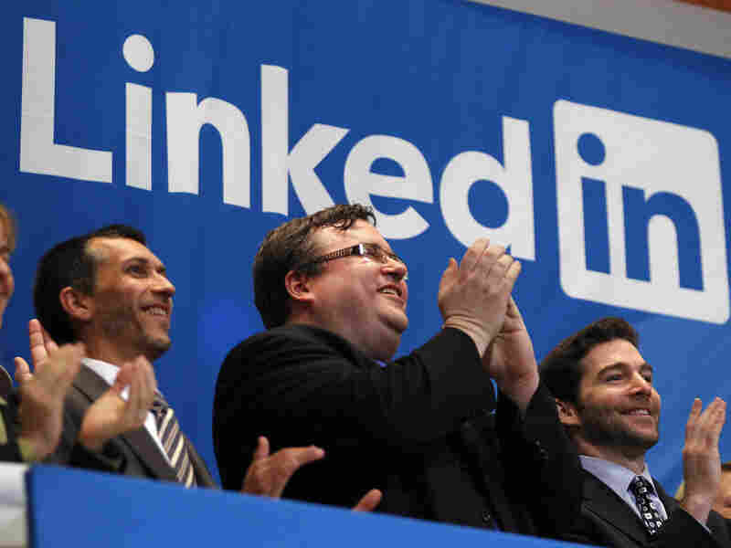 Reid Garrett Hoffman (center), the founder of LinkedIn, applauds from the bell balcony after the opening bell during the company's initial public offering at the New York Stock Exchange.