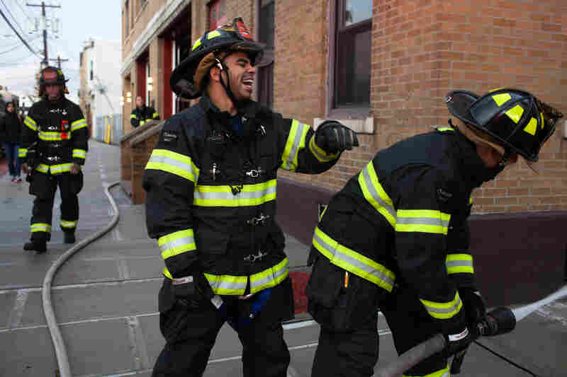 Probationary firefighters Victor Ramos (center) and Andres Godoy (right) joke during training at the 16th Street Firehouse.