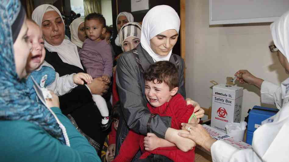 A doctor vaccinates a child against polio at a health clinic in Damascus, Syria, on Nov. 6. To stop the disease from spreading beyond Syria,  health officials plan to vaccinate 20 million children in the region.